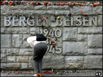 A woman lays flowers where Belsen once stood