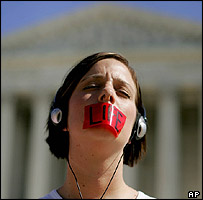 A woman with 'Life' taped to her mouth stands outside the Supreme Court