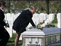 Trish Burnett places a rose on the coffin of her father's remains at Arlington cemetery