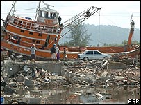 Two Indonesian refugees walk down a road covered with debris leftover from the tsunami in the west coast town of Leupung, Aceh, 09 January 2005.