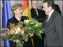 New Chancellor Angela Merkel receives flowers from the outgoing Gerhard Schroeder