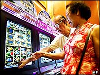 An elderly Singaporean couple checks out a slot machine at a casino and gaming expo in this June 22, 2004 file photo in Singapore