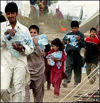 Quake survivors carrying bottled water in Balakot, Pakistan