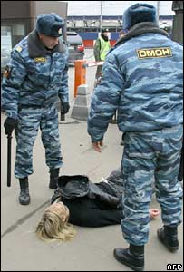Russian police remove a human rights activist protesting outside the Duma in Moscow