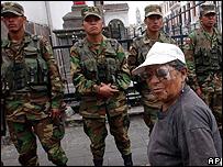 Una ecuatoriana pasa frente a soldados que vigilan el palacio presidencial en Quito
