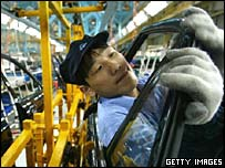 A worker fits doors on cars at a factory in Hainan