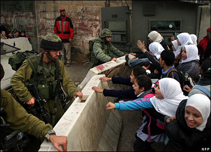 Palestinian students push the checkpoint's concrete barrier