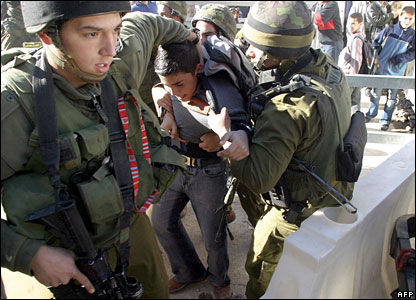 A Palestinian boy is seized by Israeli soldiers