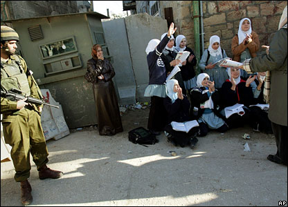 Palestinian schoolteachers hold a class next to the checkpoint