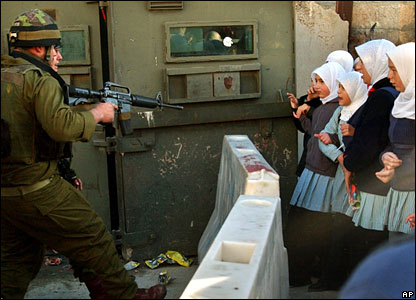 An Israeli soldier points his weapon at the protestors