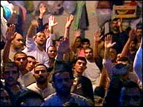 Iraqi prisoners raise their hands when asked by the BBC if they have been tortured