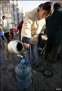 Woman collects water from a tanker in Harbin