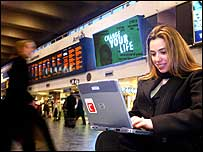 Woman using laptop at a train station