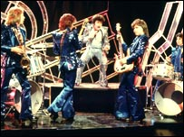 Gary Glitter (singing centre) and the Glitter Band