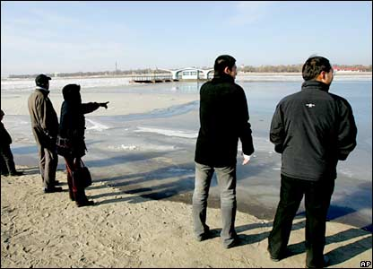 Harbin residents look at the Songhua river