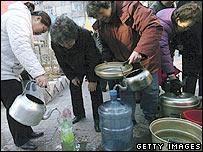 Local residents stand in line to get drinking water from a water wagon on November 23, 2005 in Harbin
