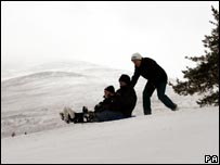 A family sledging close to Loch Morlich near Aviemore