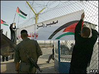 "Palestinians place a banner reading in Arabic ""Rafah crossing: Palestine's gateway to freedom"" at the entrance to the Rafah terminal"