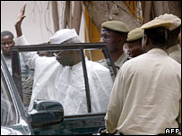 Hissene Habre waves as he gets in a car surrounded by prison guards in Senegal on 17 November 2005