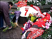 A fan placing a floral tribute to George Best