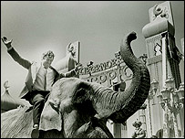 Geoffrey Thompson rides an elephant for a ride opening in 1989