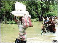 Indian villagers carry possessions over flood water.  Image: AFP/Getty