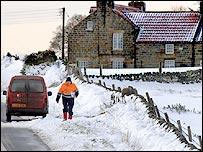 A postman walking in snow near Whitby