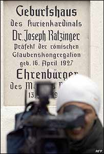 A cameraman shoots footage in front of a plaque commemorating the birth of Joseph Ratzinger