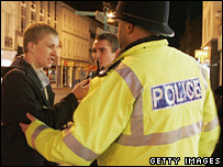 Police speak to a man during an operation to enforce new licensing laws
