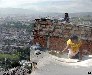Mujer barre ceniza del techo de su casa