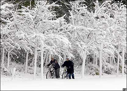 Jan Enk (left) and Kevin Altinkeyer push their bicycles through the snow in Gelsenkirchen, Germany.