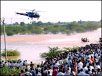 Crowds watch as a helicopter hovers over the scene of an accident