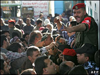 Palestinian policemen try to control people waiting for their passports to be checked at Rafah terminal