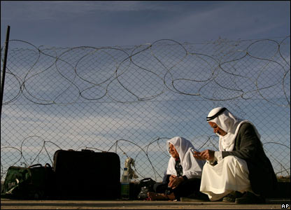 A Palestinian couple sits next to their luggage as they wait to cross into Egypt at the Rafah border