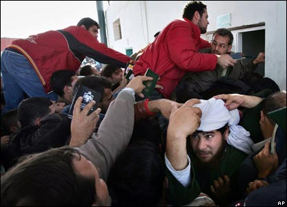 Palestinians rush to get their passports checked before entering the Rafah border terminal