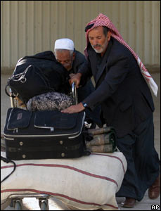 Palestinians push their luggage as they arrive to the Rafah border crossing