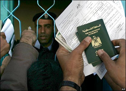 Palestinians hold their passports to be checked at the passport control terminal at Rafah