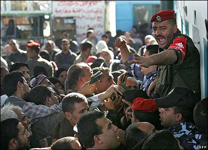 Palestinian policemen try to control the crowd of people waiting for their passports to be checked