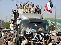 Iraqis gather round a truck carrying the corpses