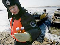 An environment officer collects samples from the Songhua River