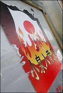 """Cartel en el que se ve la bandera japonesa en llamas y se lee en chino """"váyanse al diablo""""."""