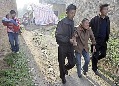 Zhang Jinju breaks down as she is helped away from the funeral parlour, where her brother's body is kept.