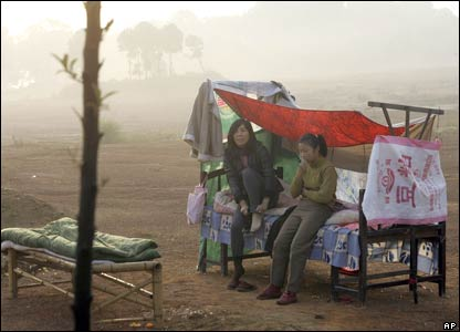 Residents sit at a makeshift bed after an earthquake struck central China on Saturday