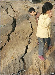 Children play near cracks in the ground near Ruichang