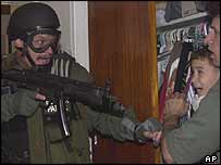 US federal officer pointing gun at Elian and man holding him