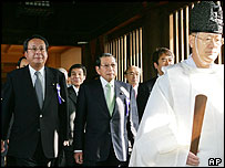 A group of Japanese lawmakers follow a Shinto priest as they pay homage at Yasukuni shrine in Tokyo