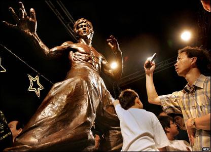 Un joven toma con su celular una foto de la estatua de Bruce Lee en Hong Kong.