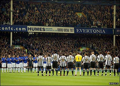 The players of Newcastle and Everton lead the minute of applause as a tribute to Best