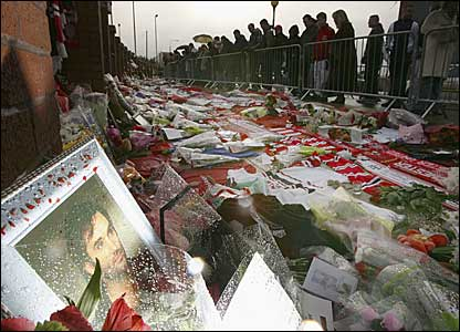 People stand and look at the sea of tributes outside Old Trafford