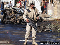 A US soldier surveys the aftermath of a Baghdad car bomb